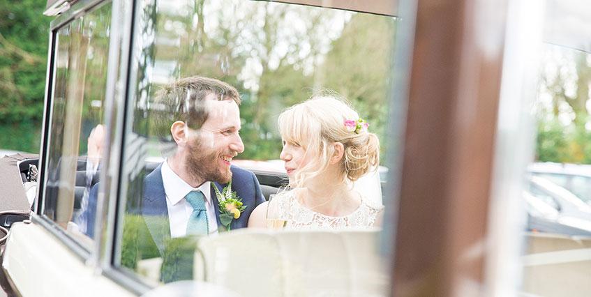 Blonde bride and bearded groom in wedding car