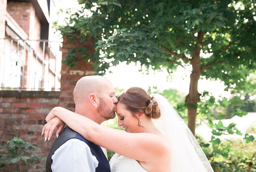 groom kissing bride on forehead summer wedding