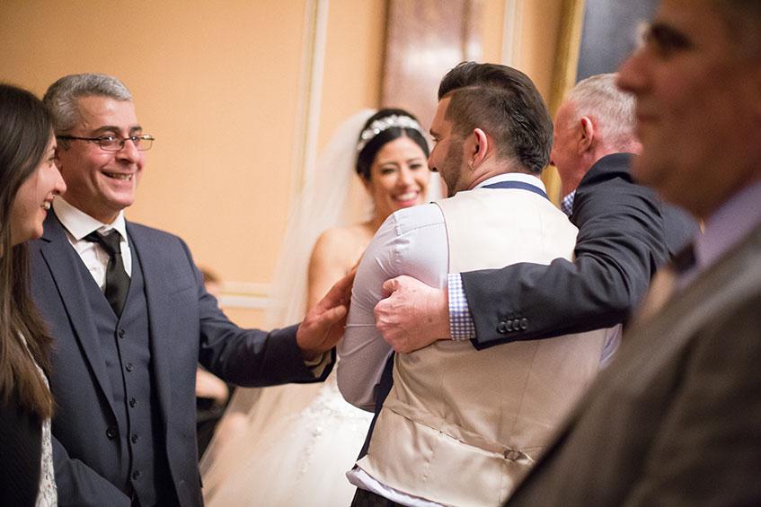 men hugging at wedding