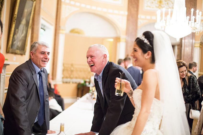 two men laughing at brides joke at wedding