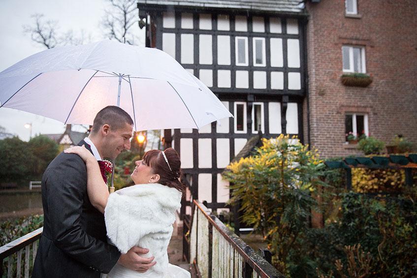 bride and groom under umbrella at raining wedding