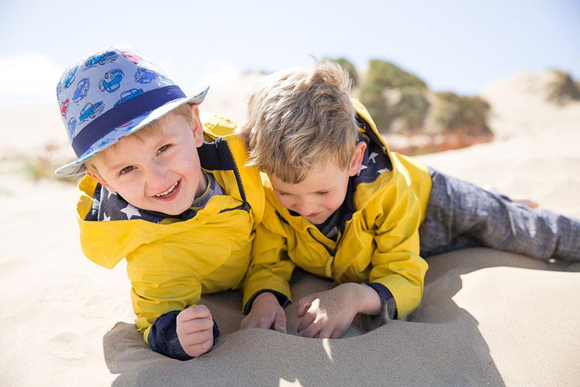 boys in yellow coats on beach