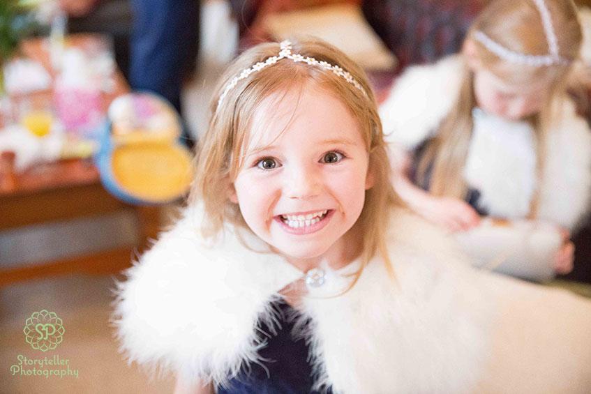 Flower girl smiling wearing a faux fur bolero
