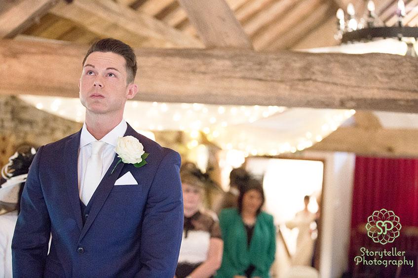 groom in navy suit getting emotional as his bride walks in the aisle