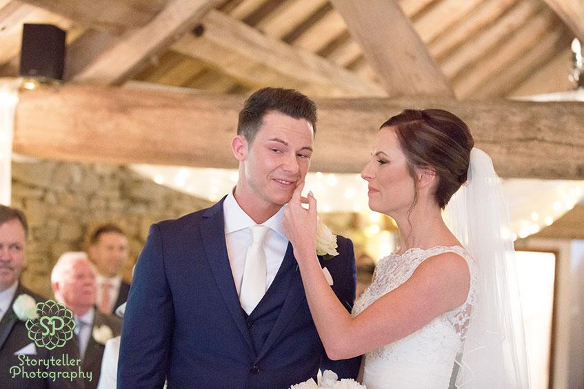 barn style wedding with beams. Bride wipes away grooms tears