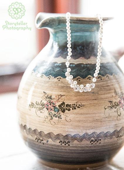 Bridal necklace details hanging in vase