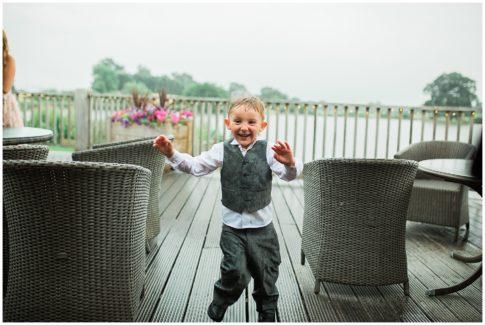 Little boy at Sandhole Oak Barn Wedding , running inside smiling from the heavy rain