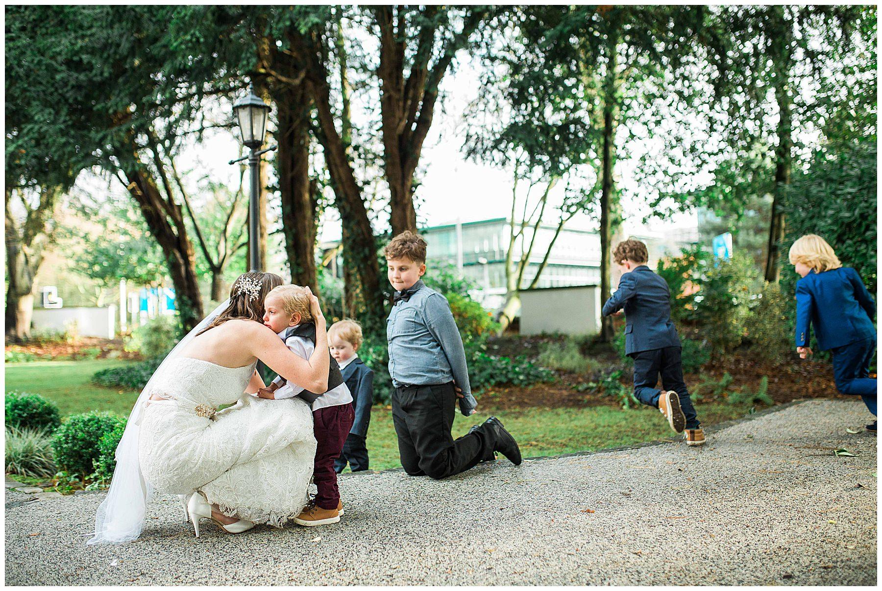 Bride hugs her son whilst children play around them